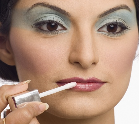 Persons hand applying lipstick on a young womans lips