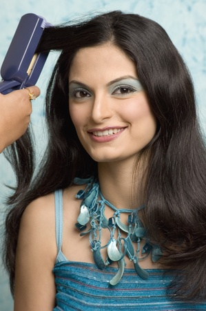 photosindia: Persons hand ironing a young womans hair