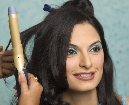 photosindia: Persons hand curling a young womans hair