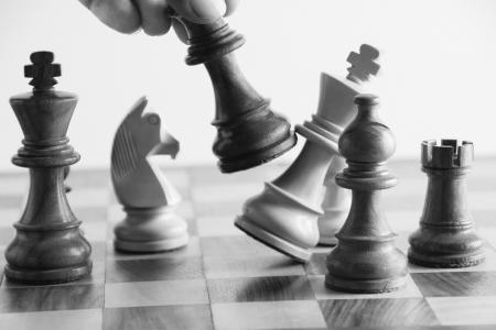 ajedrez: Mano de la persona, derrotando a un rey en el juego de ajedrez Foto de archivo