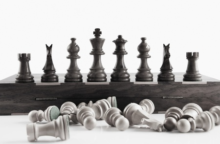 White chess pieces fell in front of black chess pieces Stock Photo