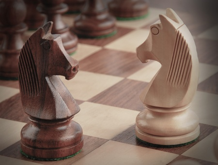 Knights facing each other on a chess board Stock Photo - 10126050