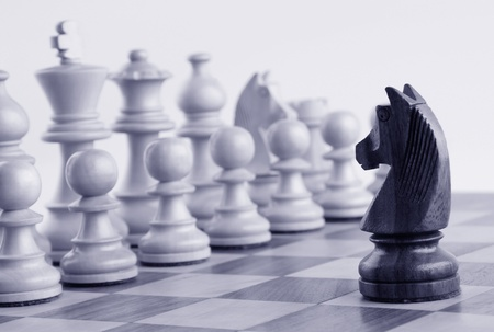 Black knight facing white chess pieces on a chess board photo