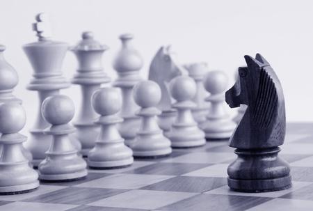Zwarte ridder geconfronteerd met witte schaakstukken op een schaakbord Stockfoto