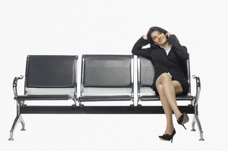 rfbatch15: Businesswoman sitting on an armchair and talking on a mobile phone LANG_EVOIMAGES