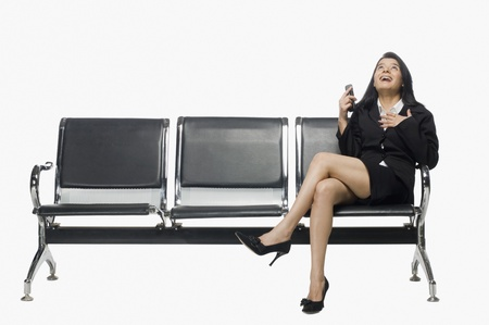 rfbatch15: Businesswoman sitting on an armchair and looking up with excitement