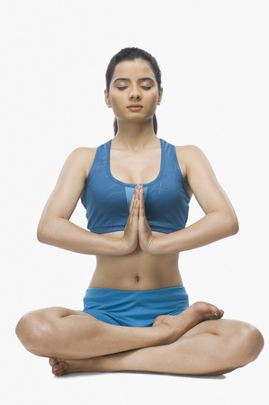 self conscious: Young woman practicing yoga against white background LANG_EVOIMAGES