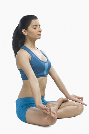 photosindia: Young woman practicing yoga against white background LANG_EVOIMAGES