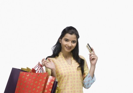 rfbatch15: Young woman holding shopping bags and showing a credit card LANG_EVOIMAGES