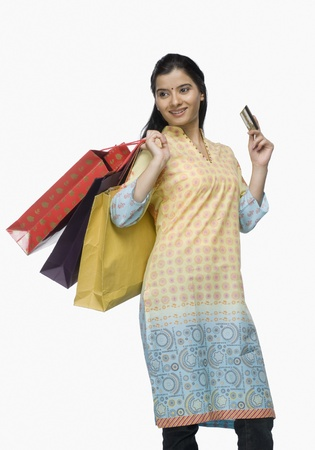 photosindia: Young woman holding shopping bags and showing a credit card LANG_EVOIMAGES