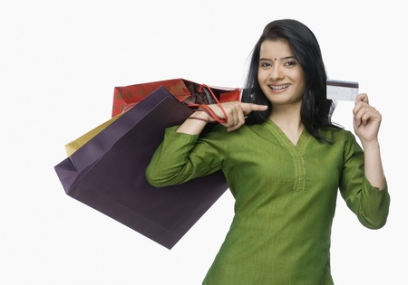 shopper: Young woman holding shopping bags and showing a credit card LANG_EVOIMAGES