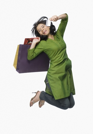 rfbatch15: Young woman jumping with shopping bags and a credit card