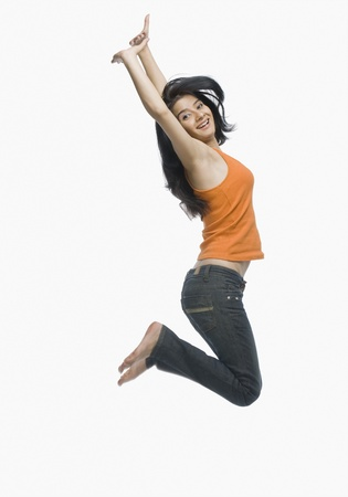 Young woman jumping against white background Stock Photo