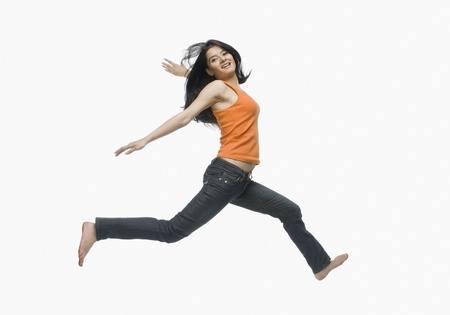 photosindia: Young woman jumping against white background LANG_EVOIMAGES