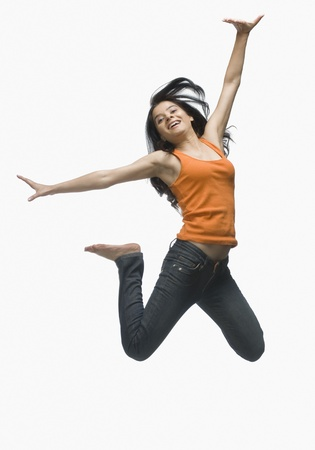 Young woman jumping against white background 스톡 콘텐츠