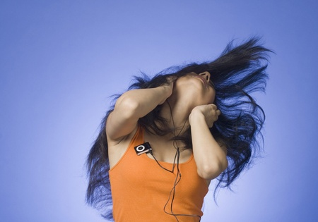 rfbatch15: Young woman listening an MP3 player against blue background LANG_EVOIMAGES