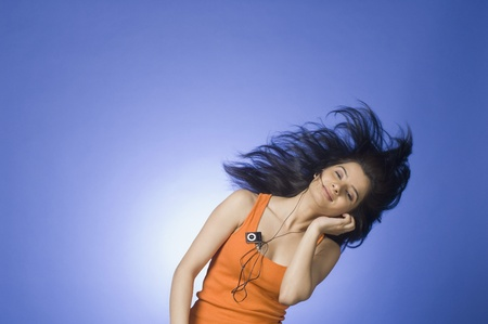 photosindia: Young woman listening an MP3 player against blue background LANG_EVOIMAGES