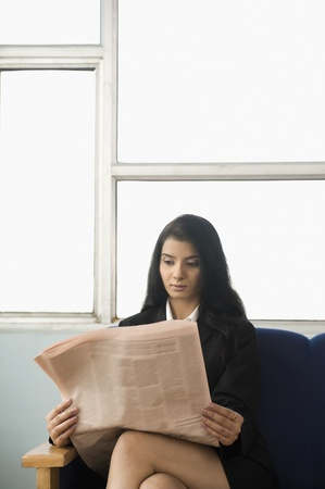 legs crossed at knee: Businesswoman reading a financial newspaper