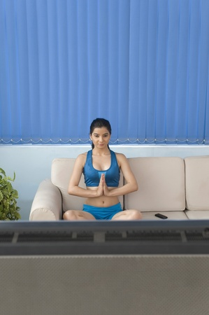 meditation help: Young woman practicing yoga in front of television