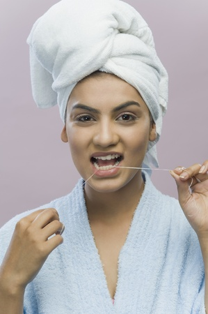 Portrait of a young woman flossing her teeth Stock Photo - 10126059