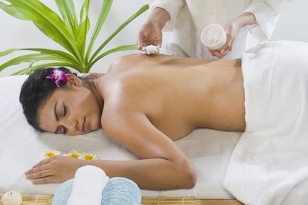 Massage therapist applying massage cream on a young woman's back Stock Photo - 10123767
