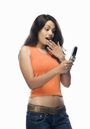 Shocked young woman reading text message