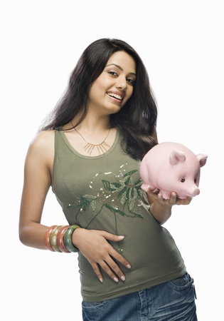 Portrait of a young woman holding a piggy bank Stock Photo - 10126112