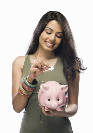 putting up: Young woman putting a coin into a piggy bank LANG_EVOIMAGES