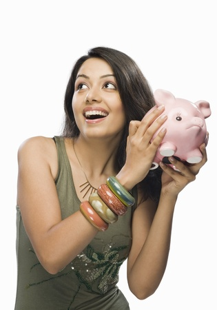 budgeting: Young woman shaking a piggy bank LANG_EVOIMAGES