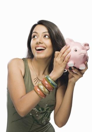 Young woman shaking a piggy bank 版權商用圖片