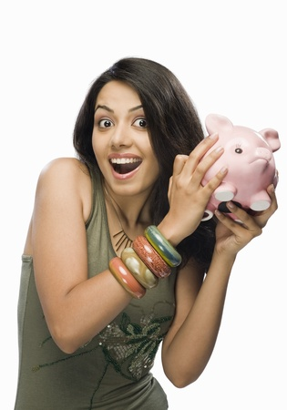 Portrait of a young woman shaking a piggy bank Stock Photo - 10126110