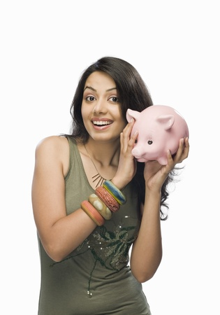 Portrait of a young woman shaking a piggy bank Stock Photo - 10123614