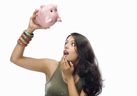 budgeting: Young woman looking at a piggy bank in shock