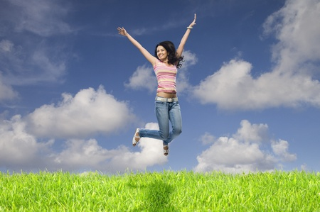 triumphing: Young woman jumping in a field LANG_EVOIMAGES