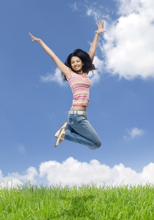 Young woman jumping in a field Stock Photo - 10123724