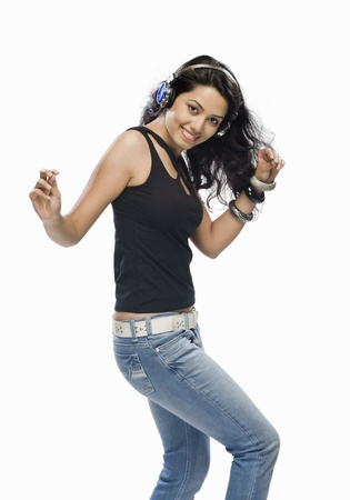Young woman listening to music and dancing Stock Photo - 10123547