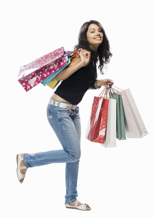 retail therapy: Portrait of a young woman holding shopping bags LANG_EVOIMAGES