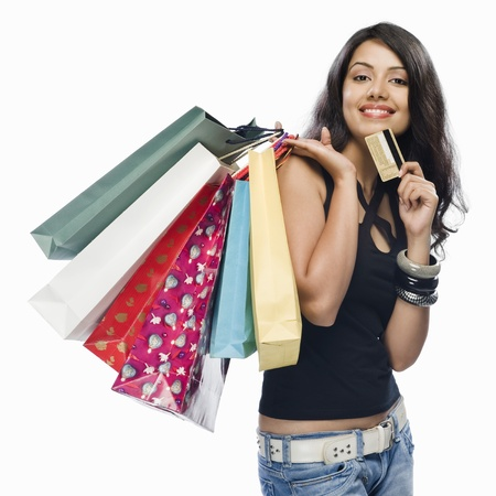 happy shopping: Portrait of a young woman holding shopping bags and a credit card LANG_EVOIMAGES