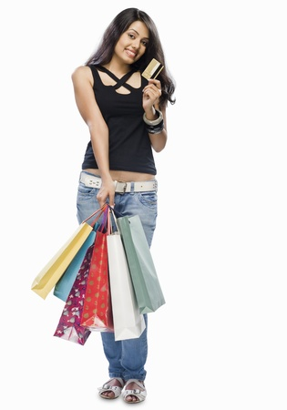 top: Portrait of a young woman holding shopping bags and showing a credit card