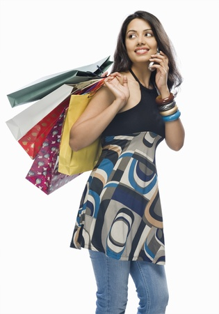 retail therapy: Young woman holding shopping bags and talking on a mobile phone LANG_EVOIMAGES