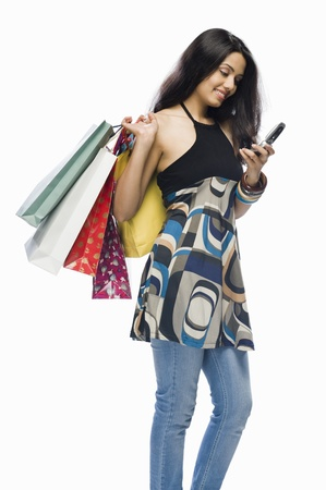 retail therapy: Young woman holding shopping bags and a mobile phone