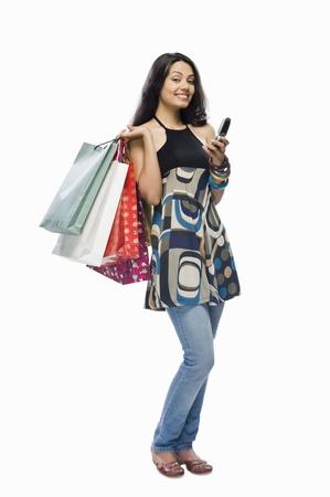 Portret van een jonge vrouw met boodschappentassen en een mobiele telefoon