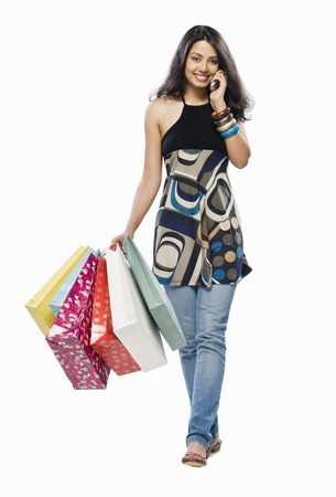 Portrait of a young woman holding shopping bags and talking on a mobile phone Stock Photo - 10126282