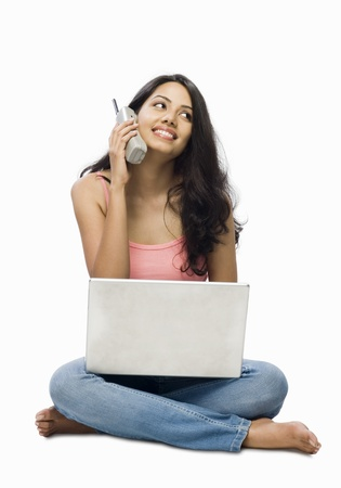Young woman using a laptop and talking on a cordless phone Stock Photo