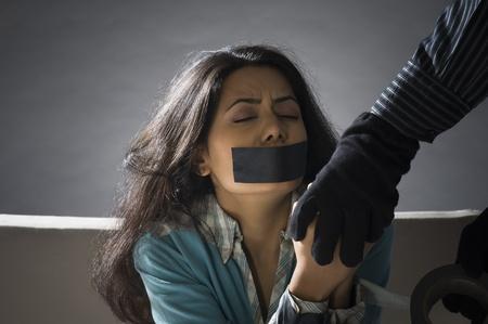 imbavagliare: Mani del rapitore avvolgimento nastro adesivo intorno le mani di una donna giovane rapito