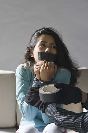 Kidnappers hands wrapping adhesive tape around an abducted young womans hands Stock Photo