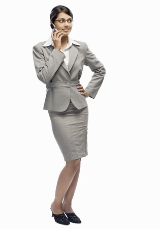 Businesswoman talking on a mobile phone against a white background Stock Photo - 10126330