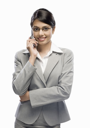 Businesswoman talking on a mobile phone against a white background Stock Photo - 10123696
