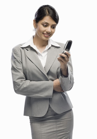Businesswoman looking at a mobile phone against a white background Stock Photo - 10126156