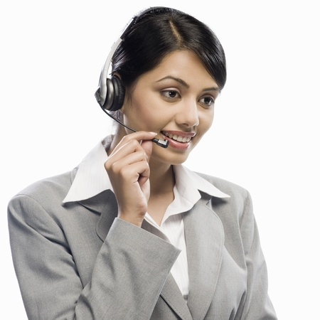Female customer care executive wearing a headset against a white background Фото со стока